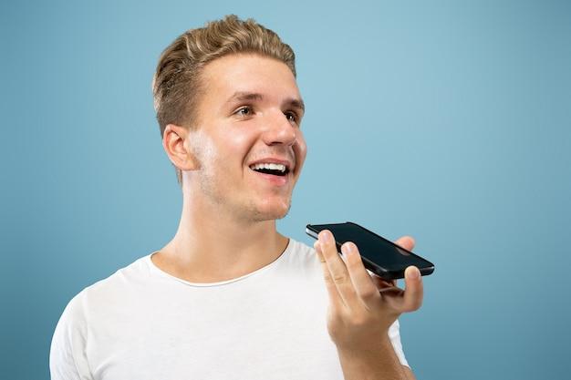 블루 스튜디오 배경에 백인 젊은 남자의 절반 길이 초상화. 셔츠에 아름 다운 남성 모델입니다. 인간의 감정, 표정, 판매, 광고의 개념. 음성 메시지를 녹음하고 웃고 있습니다.