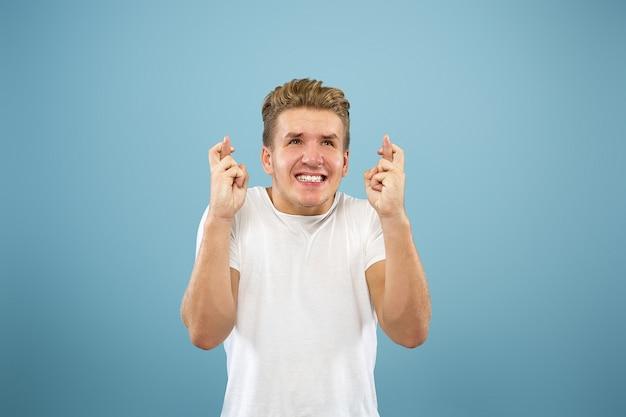 Поясный портрет кавказского молодого человека на синем фоне студии. красивая мужская модель в рубашке. концепция человеческих эмоций, выражения лица, продаж, рекламы. показываю жест удачи.
