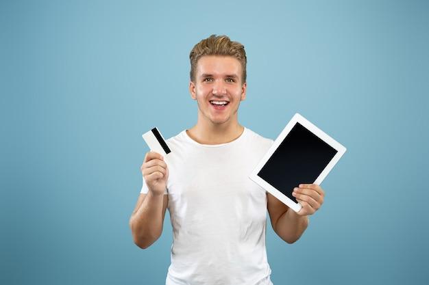블루 스튜디오 배경에 백인 젊은 남자의 절반 길이 초상화. 셔츠에 아름 다운 남성 모델입니다. 인간의 감정, 표정, 판매, 광고의 개념. 태블릿 화면과 결제 카드를 표시합니다.