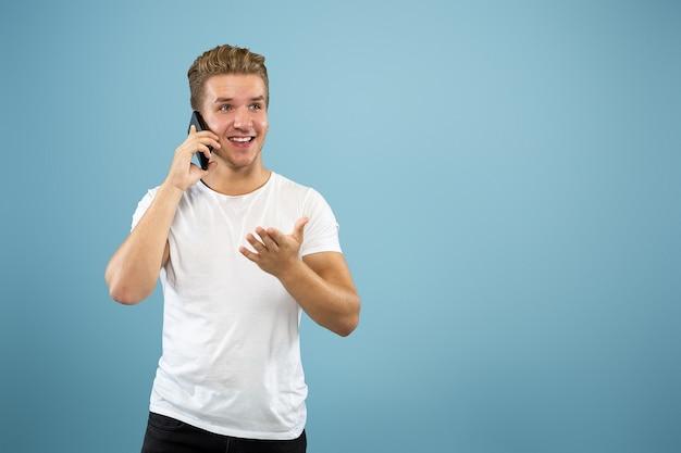블루 스튜디오 배경에 백인 젊은 남자의 절반 길이 초상화. 셔츠에 아름 다운 남성 모델입니다. 인간의 감정, 표정, 판매, 광고의 개념. 전화 통화하면 행복해 보입니다.