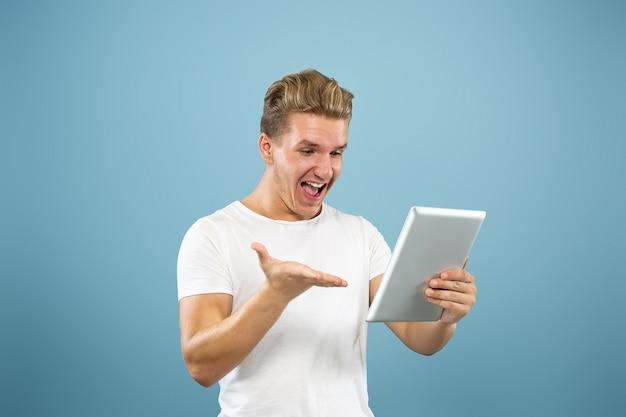 Поясный портрет кавказского молодого человека на синем фоне студии. красивая мужская модель в рубашке. концепция человеческих эмоций, выражения лица, продаж, рекламы. использование планшета для видеоблога, селфи, учебы.