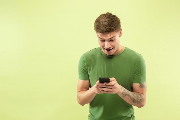 緑のスタジオの背景に白人の若い男の半分の長さの肖像画。シャツの美しい男性モデル。人間の感情、表情、販売、広告の概念。賭け、オンライン購入、ウェブサーフィン。