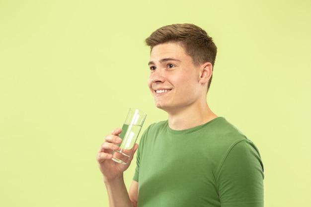 緑のスタジオの背景に白人の若い男の半分の長さの肖像画。シャツの美しい男性モデル。人間の感情、顔の表情、販売、広告の概念。純粋な水を飲むのを楽しんでいます。