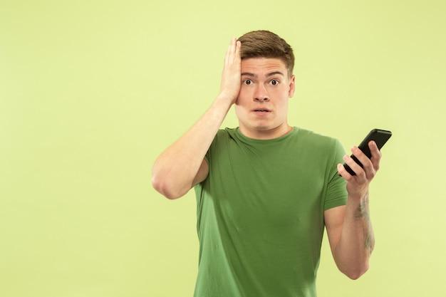 緑のスタジオの背景に白人の若い男の半分の長さの肖像画。シャツの美しい男性モデル。人間の感情、顔の表情、販売、広告の概念。電話を持って動揺しているように見えます。