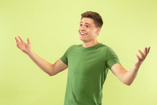 緑のスタジオの背景に白人の若い男の半分の長さの肖像画。シャツの美しい男性モデル。人間の感情、顔の表情、販売、広告の概念。笑顔、挨拶、招待。