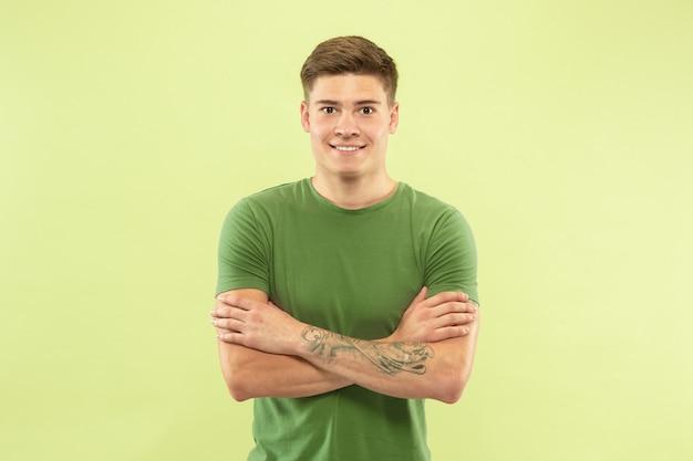 녹색 스튜디오 배경에 백인 젊은 남자의 절반 길이 초상화. 셔츠에 아름 다운 남성 모델입니다. 인간의 감정, 표정, 판매, 광고의 개념. 손으로 서 넘어, 웃 고.