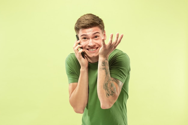 緑のスタジオの背景に白人の若い男の半分の長さの肖像画。シャツの美しい男性モデル。人間の感情、表情、販売、広告の概念。電話で話していると幸せそうに見えます。