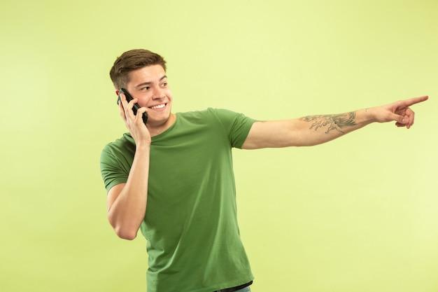 녹색 스튜디오 배경에 백인 젊은 남자의 절반 길이 초상화. 셔츠에 아름 다운 남성 모델입니다. 인간의 감정, 표정, 판매, 광고의 개념. 전화로 얘기하고 가리키는, 웃고.