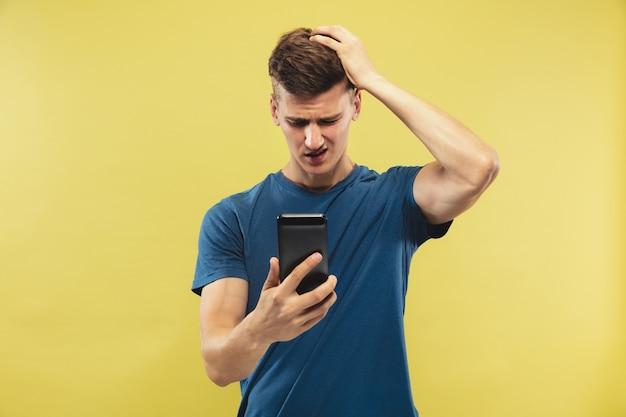 Поясной портрет кавказского молодого человека на желтом пространстве. красивая мужская модель в голубой рубашке