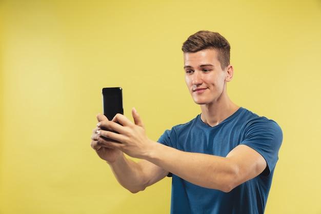 Поясной портрет кавказского молодого человека на желтом фоне студии. красивая мужская модель в голубой рубашке. понятие о человеческих эмоциях, выражении лица. делает селфи или видеоблог, выглядит счастливым.