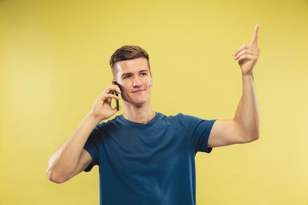 Поясной портрет кавказского молодого человека на желтом фоне студии. красивая мужская модель в голубой рубашке. понятие о человеческих эмоциях, выражении лица. говорим по телефону, есть идея.