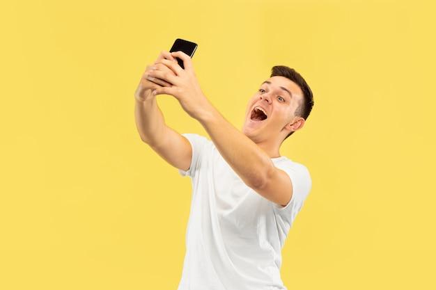 Поясной портрет кавказского молодого человека на желтом фоне студии. красивая мужская модель в рубашке. концепция человеческих эмоций, выражения лица, продаж, рекламы. делает селфи или контент для своего видеоблога.