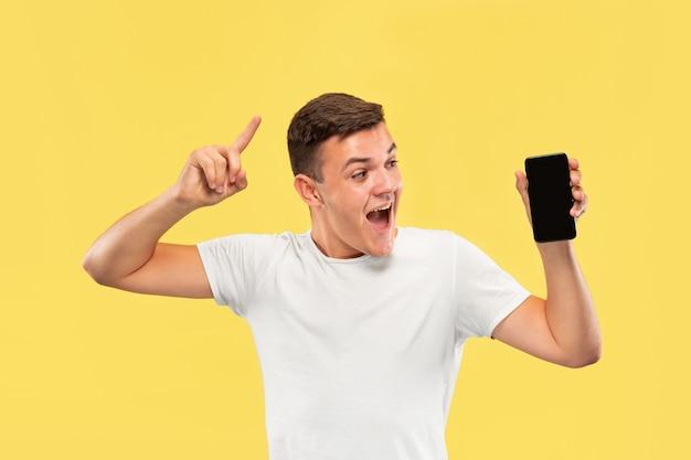 Поясной портрет кавказского молодого человека на желтом фоне студии. красивая мужская модель в рубашке. концепция человеческих эмоций, выражения лица, продаж, рекламы. показываю экран телефона и улыбаюсь.
