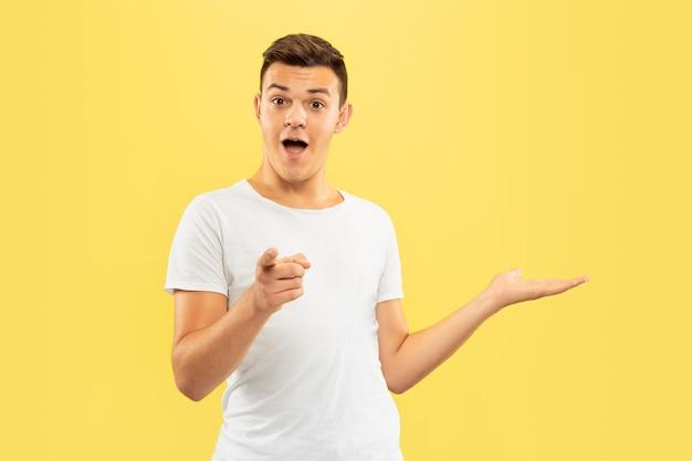 黄色のスタジオで白人の若い男の半分の長さの肖像画