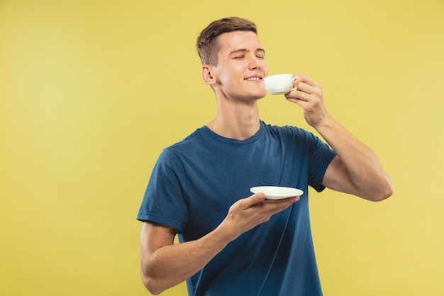 Caucasian young man's half-length portrait on yellow studio background. beautiful male model in blue shirt. concept of human emotions, facial expression. enjoying drinking coffee or tea.