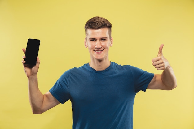 Caucasian young man's half-length portrait on yellow studio background. beautiful male model in blue shirt. concept of human emotions, facial expression. holding phone and showing thumb up.