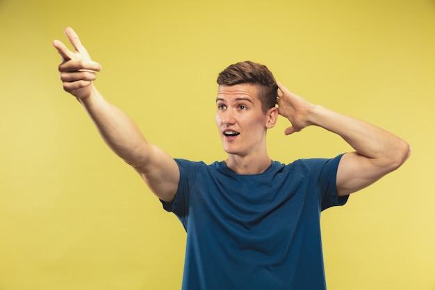 Ritratto a mezzo busto del giovane caucasico su sfondo giallo studio. bello modello maschio in camicia blu. concetto di emozioni umane, espressione facciale. mostrare e indicare qualcosa. invitante.