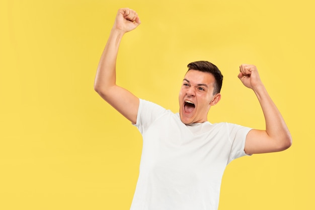 Caucasian young man's half-length portrait on yellow studio background. beautiful male model in shirt. concept of human emotions, facial expression, sales, ad. celebrating, calling, screaming.