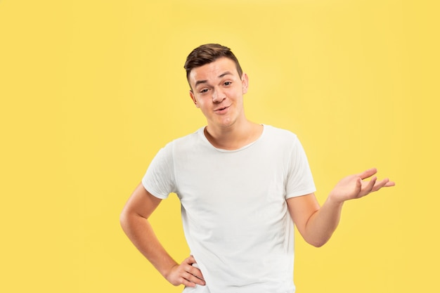 Caucasian young man's half-length portrait on yellow studio background. beautiful male model in shirt. concept of human emotions, facial expression, sales, ad. showing something, copyspace.