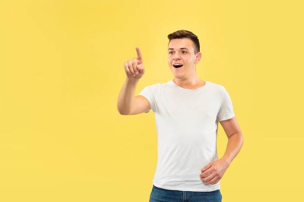 Caucasian young man's half-length portrait on yellow studio background. beautiful male model in shirt. concept of human emotions, facial expression, sales, ad. touching an empty search bar.