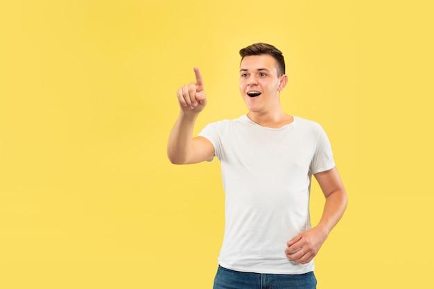 Ritratto a mezzo busto del giovane caucasico su sfondo giallo studio. bellissimo modello maschile in camicia. concetto di emozioni umane, espressione facciale, vendite, annuncio. toccando una barra di ricerca vuota.