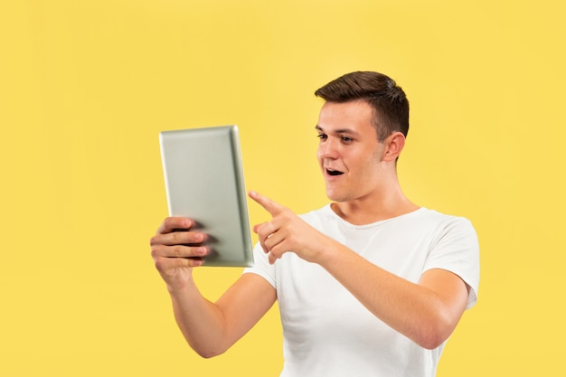 Caucasian young man's half-length portrait on yellow studio background. beautiful male model in shirt. concept of human emotions, facial expression, sales, ad. using tablet and looks happy.
