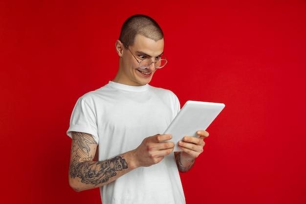 赤いスタジオの壁に分離された白人の若い男の肖像画。デバイス、ガジェットを備えた美しい男性モデル。人間の感情、顔の表情、販売、広告、技術の概念