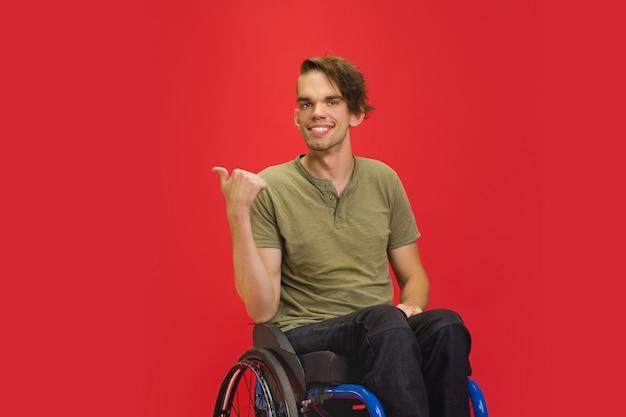 赤いスタジオで白人の若い男の肖像画。人間の感情の概念