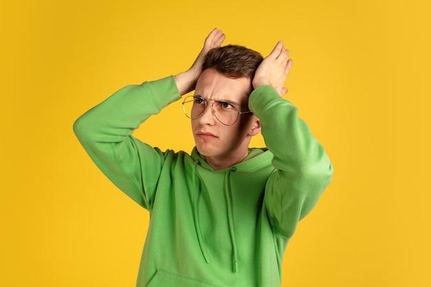 노란색 벽에 백인 젊은 남자의 초상화. 녹색 옷 몸짓에 아름 다운 남성 모델입니다. 인간의 감정, 표정, 판매, 광고, 청소년의 개념. copyspace.