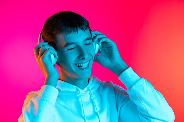 Caucasian young man's portrait on pink in neon.