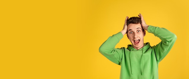 Caucasian young man's portrait on yellow  wall. beautiful male model in green outfit gesturing. concept of human emotions, facial expression, sales, ad, youth. copyspace.