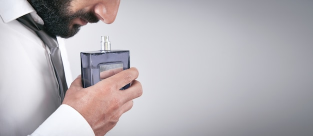 Caucasian young man smelling perfume.