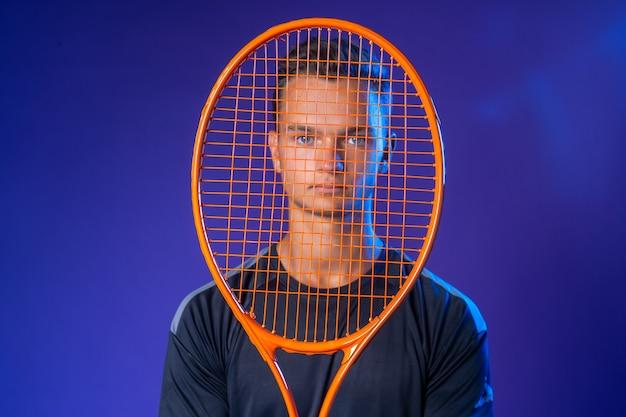 Кавказский молодой человек-теннисист позирует с теннисной ракеткой на фиолетовом фоне
