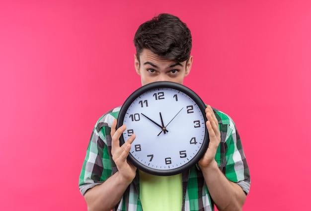 緑のシャツを着ている白人の若い男は、孤立したピンクの壁に壁時計で口を覆った