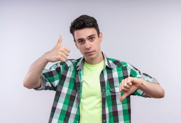 緑のシャツを着ている白人の若い男は、孤立した白い壁に親指を上下に