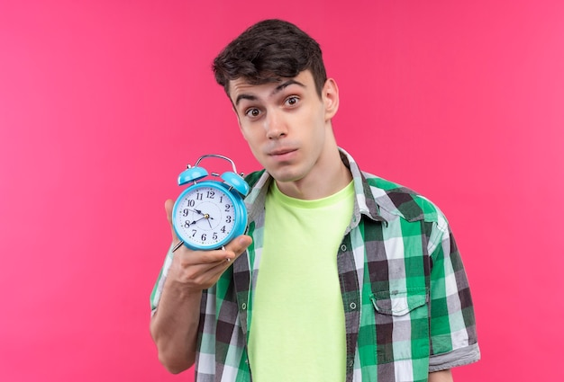 孤立したピンクの壁に目覚まし時計を保持している緑のシャツを着ている白人の若い男
