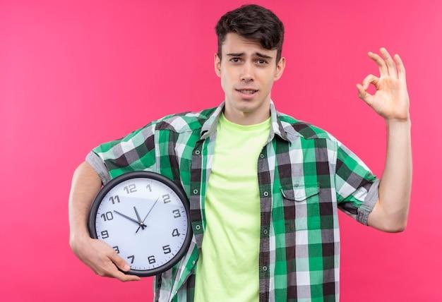 Giovane caucasico che indossa la camicia verde che tiene l'orologio da parete e che mostra il gesto okey sulla parete rosa isolata