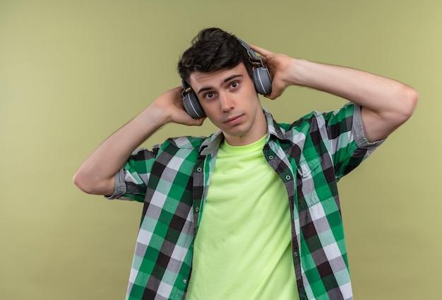 Il giovane caucasico che indossa la camicia verde ascolta la musica sulle cuffie sulla parete verde isolata