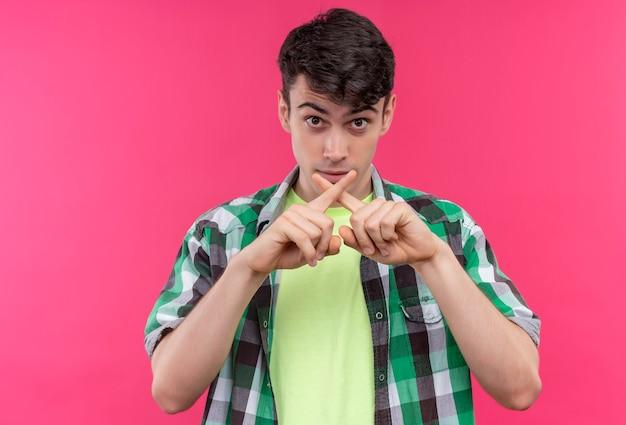 孤立したピンクの壁にジェスチャーを示さない緑のシャツを着ている白人の若い男