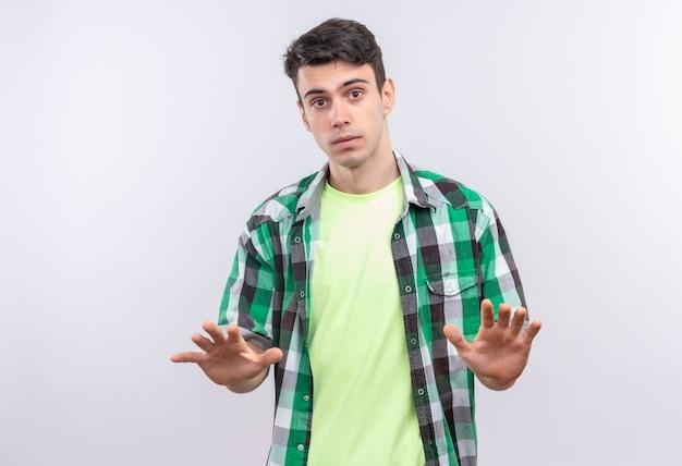 Кавказский молодой человек в зеленой рубашке показывает жест стоп на изолированной белой стене