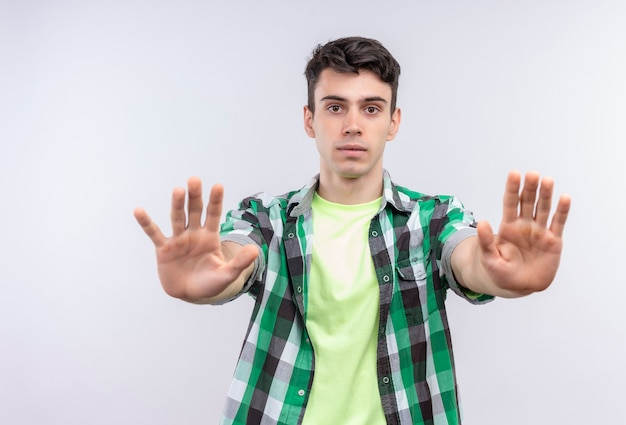 Caucasian young man wearing green shirt showing stop gesture with both hands on isolated white wall