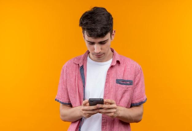 Giovane caucasico che indossa il numero di composizione della camicia rosa sul telefono sulla parete arancione isolata