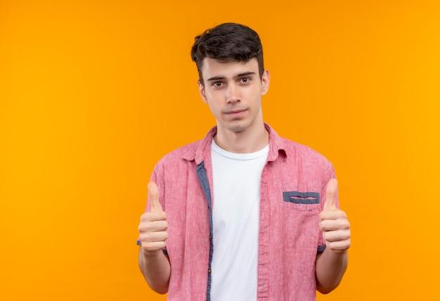 Кавказский молодой человек в розовой рубашке показывает палец вверх на изолированной оранжевой стене