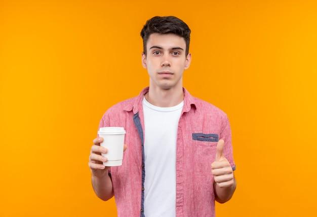 孤立したオレンジ色の壁に彼の親指をコーヒーのカップを保持しているピンクのシャツを着ている白人の若い男