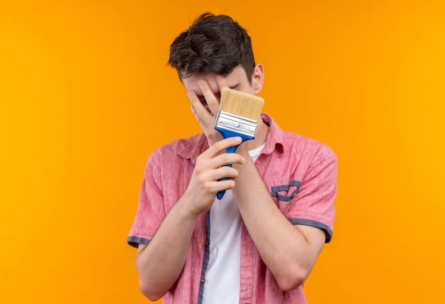 孤立したオレンジ色の壁に手でペイントブラシで覆われた顔を保持しているピンクのシャツを着ている白人の若い男