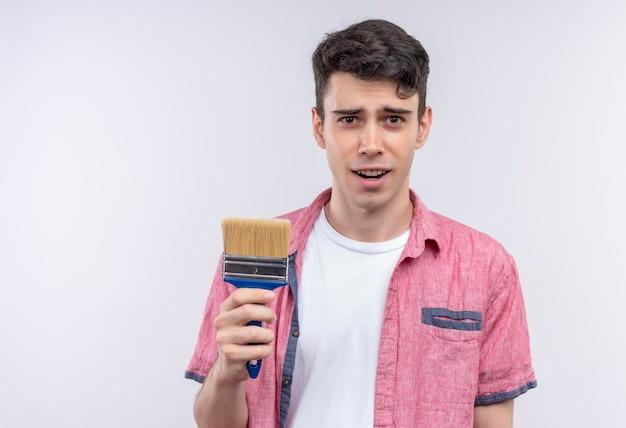孤立した白い壁にペイントブラシを保持しているピンクのシャツを着ている白人の若い男