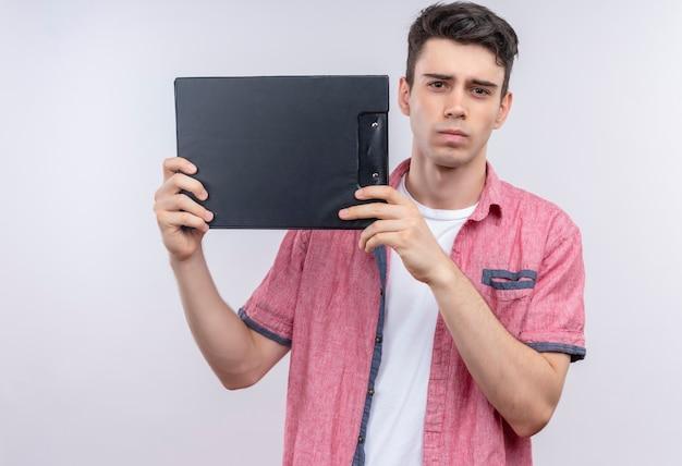 孤立した白い壁にクリップボードを示すピンクのシャツを着ている白人の若い男