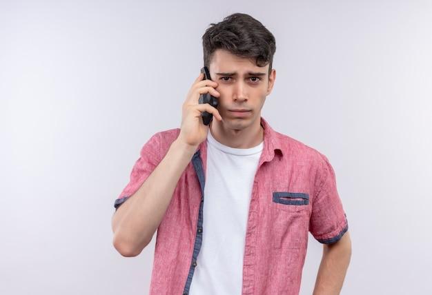 Il giovane caucasico che indossa la camicia rosa parla sul telefono sul muro bianco isolato