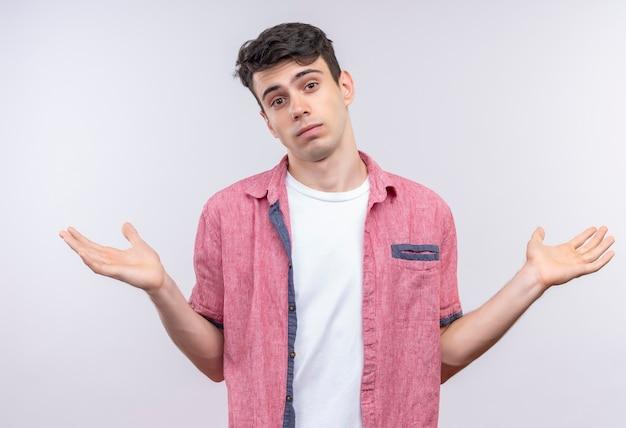 Il giovane caucasico che indossa la camicia rosa allarga le mani sul muro bianco isolato