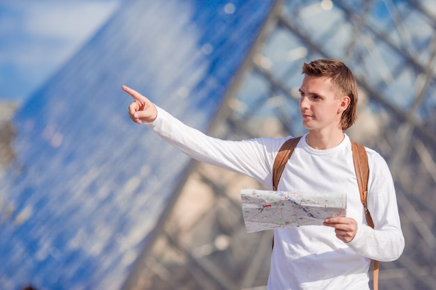 Caucasian young man with map in european city outdoors